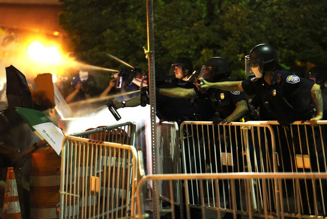 """Rochester Police officers use pepper spray, to disperse demonstrators during a protest over the death of Daniel Prude, on September 03, 2020, in Rochester, New York. Prude died after being arrested on March 23, by Rochester police officers who had placed a """"spit hood"""" over his head and pinned him to the ground while restraining him. Mayor Warren announced today the suspension of seven officers involved in the arrest. (Michael M. Santiago/Getty Images/TNS)"""