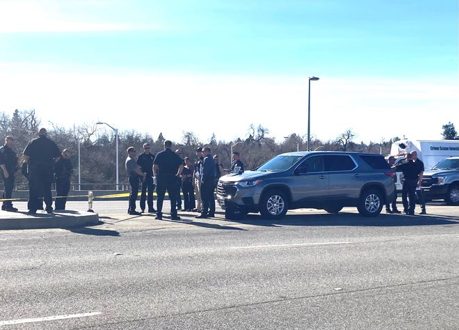 Law enforcement officers investigate a fatal officer-involved shooting on the Cypress Avenue Bridge on Sunday.