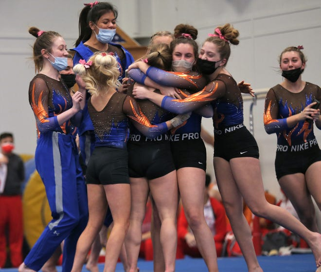 The San Angelo Central High School girls gymnastics team swarms Madison Vogel after she scored a perfect 10.0 on floor during an optional meet against the Ector County ISD in San Angelo on Saturday, Feb. 6, 2021.