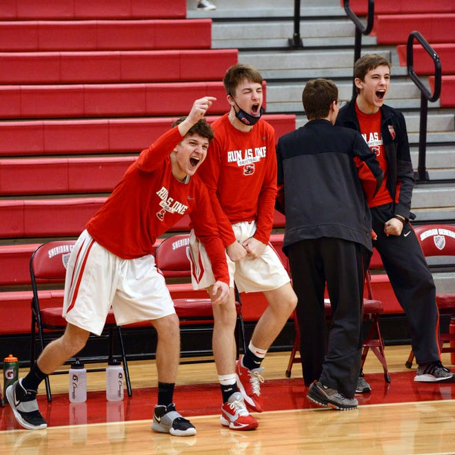 Sheridan's bench celebrates Nate Johnson's three-point play against Lancaster on Feb. 6 in Thornville.