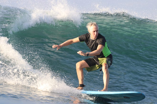 Mike Downey rides a wave on a beach in El Salvador.