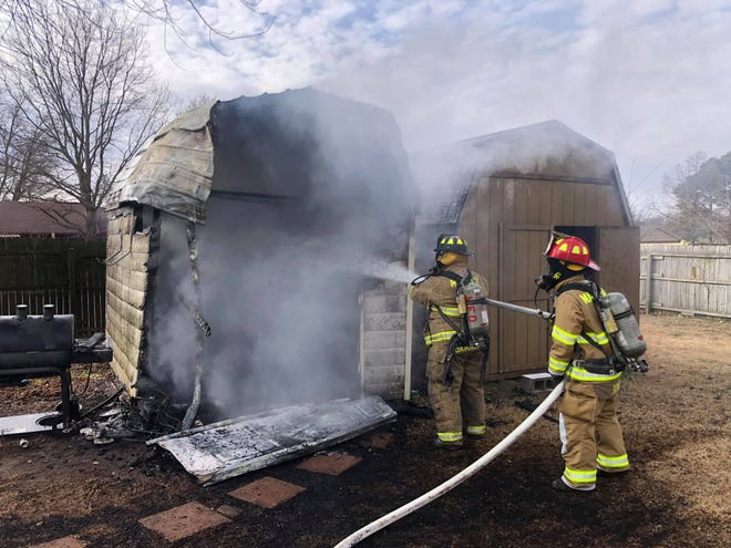 Firefighters work to put out a shed fire in Marietta Friday morning. A Marietta police officer reportedly alerted fire units after coming across the fire while on patrol.