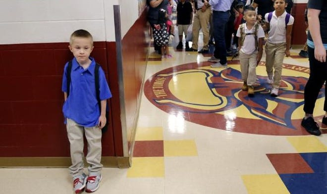 "A boy stands against the wall in the main hallway of Cesar Chavez Elementary in Oklahoma City on the first day of school in 2018. Gov. Kevin Stitt and Republican lawmakers say they support changing the way school funding is distributed to avoid dedicating money to ""ghost students."""