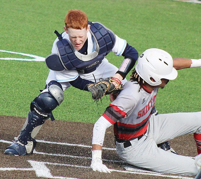 Bartlesville High's Eric Olenberger, left, tries to make a play at the plate during varsity baseball action last season.