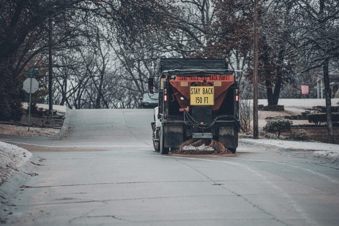 A city truck applies a sand-and-salt mixture to the road Monday as Bartlesville was hit by wintry weather. Freezing drizzle left streets slick and hazardous, especially on bridges and overpasses.