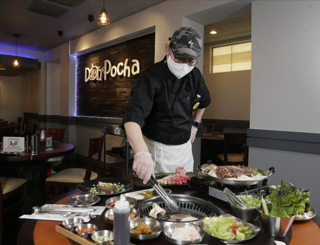 Owner and chef Jo Chong cooks on a grill table in the dining room at Korean barbecue restaurant Don Pocha.