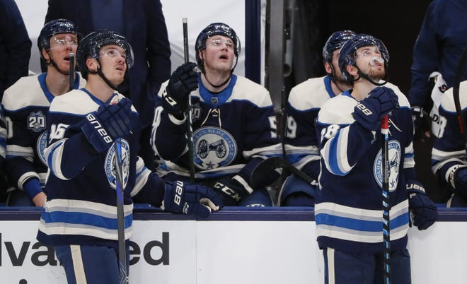 Blue Jackets players, including Jack Roslovic left, and Oliver Bjorkstrand, watch replays of a Carolina goal that was allowed to stand despite video evidence showing the Hurricanes were offside at the start of the play.