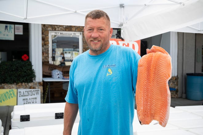 John Goguen of 2 J's Seafood holds  one of his most popular fish filets available at the Clermont Farmer's Market on Sunday.