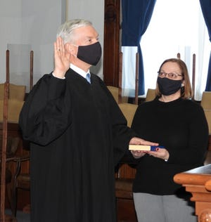 Guernsey County Common Pleas Court Judge Daniel Padden, r, administers the oath of office to re-elected Probate/Juvenile Court Judge David Bennett while Bennett's wife, Debi, holds the Bible during a small ceremony on Feb. 3 at the Guernsey County Courthouse.