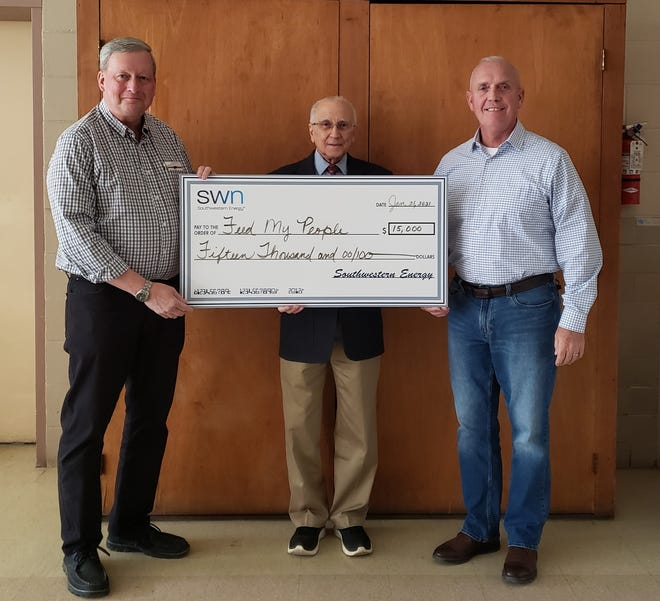 Accepting a $15,000 donation from Southwestern Energy for Feed My People were, l to r, Guernsey County Commissioner Skip Gardner, Feed My People President Bernie Schreiner and Commissioner Jack Marlin. The money will be used to remodel kitchen in order to serve more hungry individuals and families.