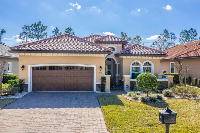 A paver driveway and walkway lead to this barrel-tile-topped home in Ormond Beach's boutique gated community of IL Villaggio.
