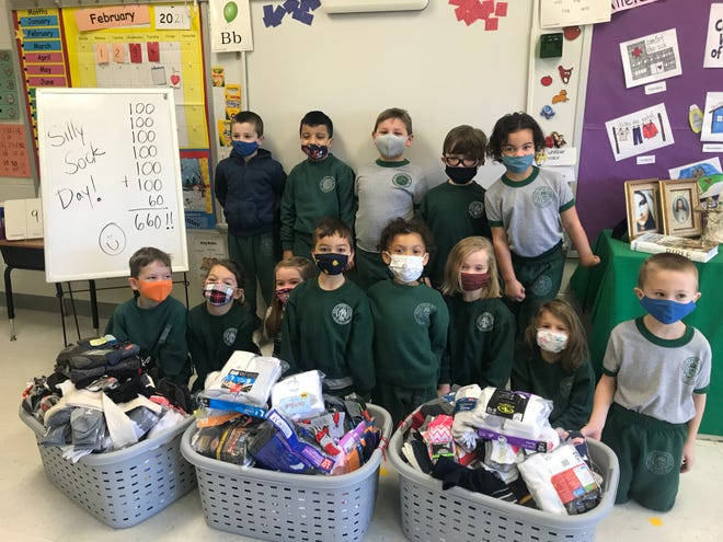 During National Catholic Schools Week, Holy Cross School donates 660 pairs of socks to Code Purple. Ann Rider's kindergarten class counted the socks as part of a math lesson to get ready for the 100th day of school.