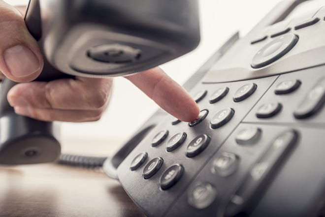 A man holds a telephone while dialing a number to make a call.