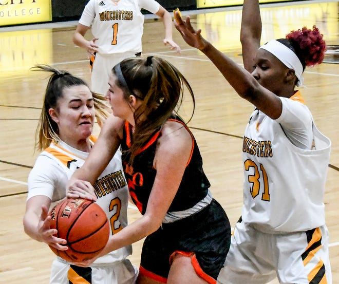 Garden City Community College's Kealani Neves, left, gets a hand on the ball and forces a turnover as she and teammate Donetria McGee apply defensive pressure to Neosho County's Lauren Jones in the backcourt Saturday at Perryman Athletic Complex.