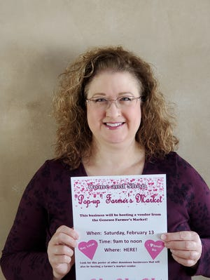 """Jill Darin, coordinator of the Geneseo Farmer's Market program, shows a poster promoting the """"Pop Up"""" Farmer's Market on Saturday in downtown Geneseo"""