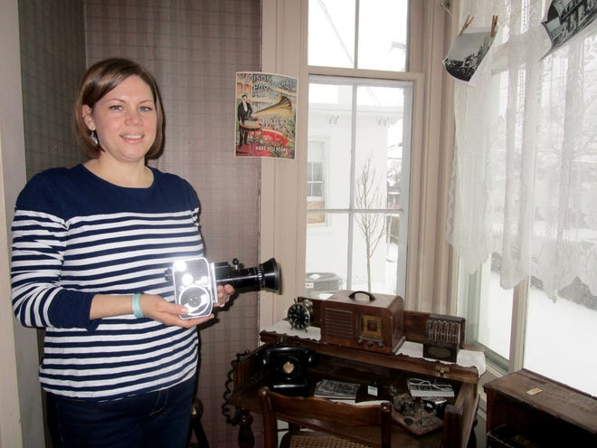 """Jennifer Bourne, director of the Geneseo Historical Museum, holds a camera from the past, which is included in the one of the newest displays at the museum. The new feature is """"Technology – Past and Present."""""""