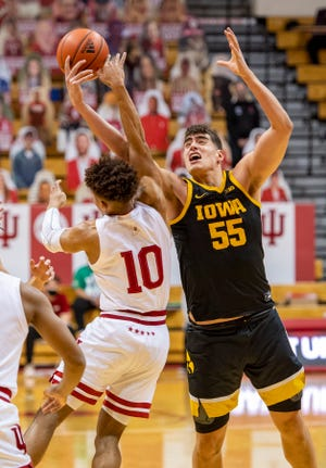 Iowa center Luka Garza (55) battles for the ball with Indiana guard Rob Phinisee (10) during Sunday's game in Bloomington, Ind.