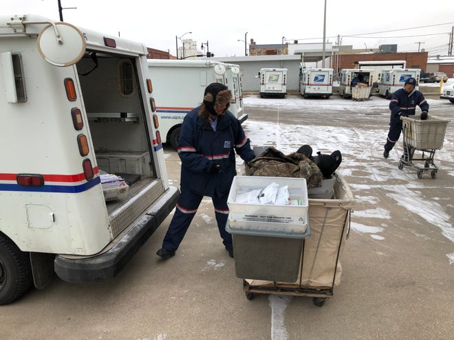 Suzanne Goatcher, a carrier for the U.S. Postal Service, loads her mail van at 706 Fort St. early Monday where the 5-degree temperature in Hays felt like minus 9 degrees, according to The Weather Channel.