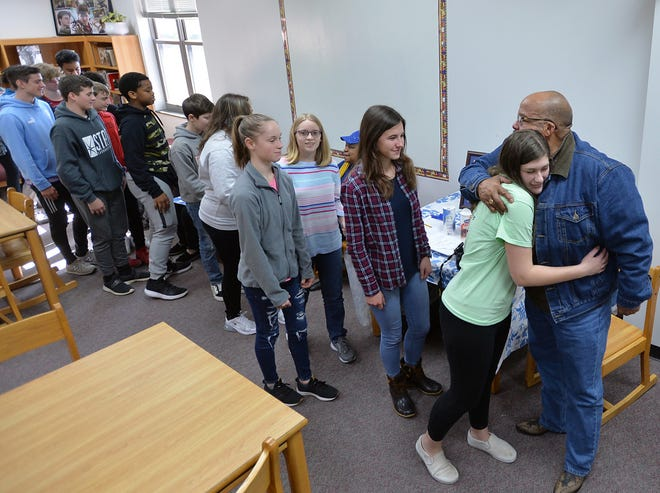 The Rev. Bobby Hill gives hugs to students Feb. 14, 2020 during the annual Ninth Avenue Day that honors the school's alumni and provides students with a chance to experience living history.