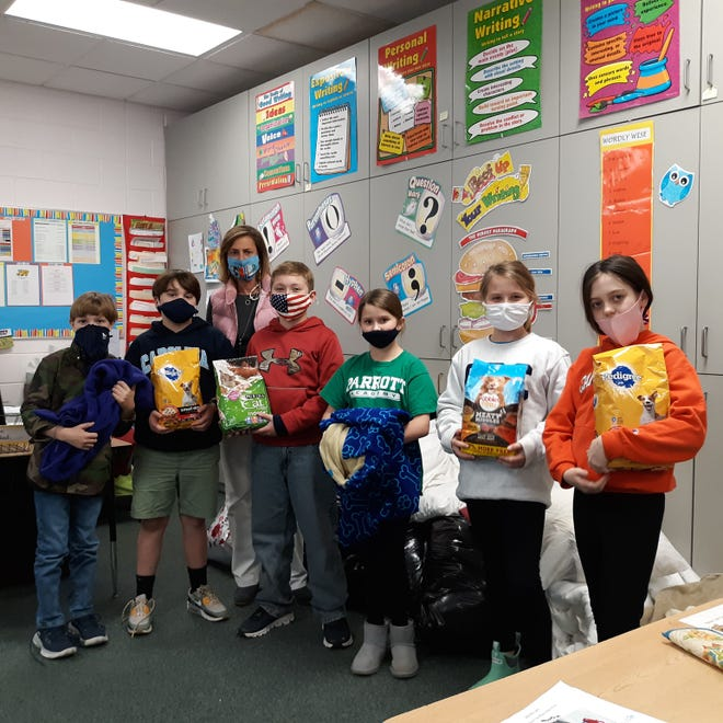 In their fourth grade classroom, Parrott students help stock a pile of donated blankets for the Lenoir County SPCA: (left to right) Mak Kilpatrick, Landon Wiggins, teacher Kimberly Whitley, Henry Sutton, Kaytyn Hughes, Madi Segrave, and Kenley Mooring. [CONTRIBUTED PHOTO]