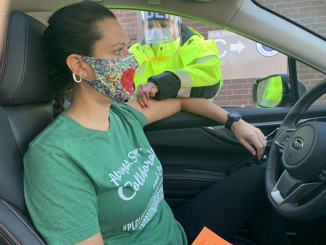 Sarah Paris, a math teacher at Nordonia High School, receives her first immunization against COVID-19. Staff with the school district were able to go to the Summit County Public Health facility on West Market in Akron to receive the vaccine in a drive-through style.