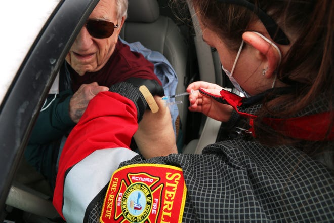 Sterling Fire Department EMT Emily Todorov, right, administers a COVID-19 vaccine to town resident Robert Dumont, left. Dumont's wife, Barbara, also received the vaccine. during the town's two-day, drive-through clinic Feb. 4 and 5.