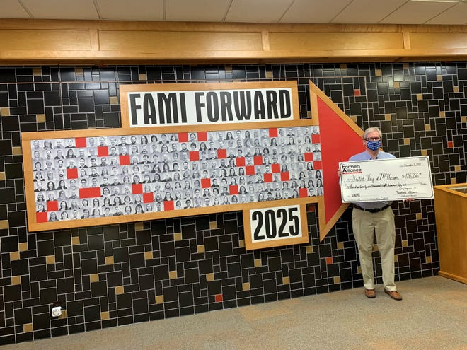 United Way of McPherson County Executive Director Rob Mackey poses with a record-breaking check from Farmers Alliance Mutual Insurance and its employees totaling $126,856.