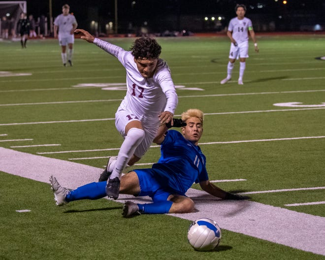 Midlothian senior Guiany Tello (11) makes a sliding challenge against Red Oak's Dakota Santos (17) during their match on Jan. 29. The Panthers stayed unbeaten in District 14-5A play with wins against Corsicana and Waco University.
