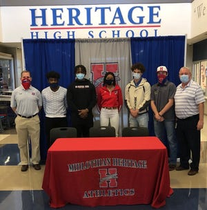 Heritage seniors Latray Miller (second from left), DeAngelo Freeman, Rachel Allen, Daelin Rader and Blake Wilhoite pose for a photo during Signing Day activities at HHS. They are joined by HHS head football coach and campus coordinator Lee Wiginton (left) and Midlothian ISD athletic director Todd York (right).