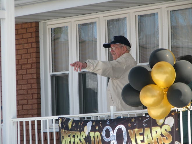 Standing on his front porch, which was adorned with banners and balloons for his 90th birthday, Conald Rogers waves to those riding by his home in a special COVID-compliant birthday parade.