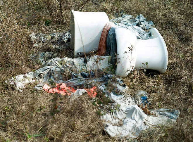 A toilet and piles of clothing and linens are strewn at a power line easement on Ponderosa Boulevard in Walton County.