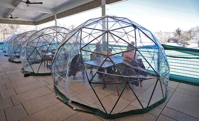 The Joyner family, of Quincy, enjoys lunch in one of the heated igloos at Weathervane in Weymouth on Monday Feb. 8, 2021.