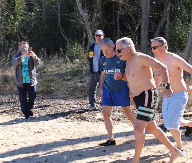 Polar Plungers from left to right, Cris Pond, Joe Klingman, and his son Mark Klingman head to plunge into the Appomattox River at City Park in Hopewell to support Special Olympics athletes on Feb. 6, 2021.
