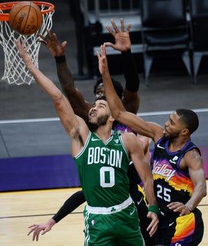 Celtics forward Jayson Tatum puts up a layup against the Suns' Mikal Bridges (25) and Deandre Ayton (22) during Sunday's game.