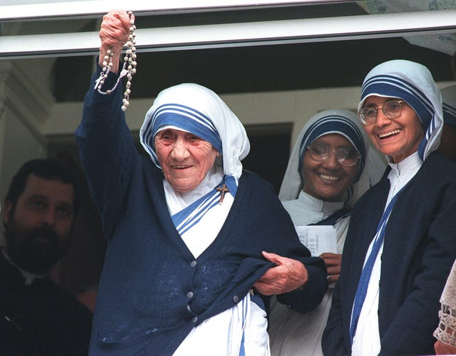 Mother Teresa holds up her rosary beads to the crowd gathered outside the Sisters of Charity convent in New Bedford, Mass., on June 14, 1995, during a U.S. visit where she met then-Bishop Sean O'Malley.