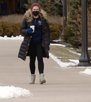 Kent State University senior Elizabeth May clutches a hot drink as she walks briskly by Risman Plaza at the university. Earlier in the day, she said she donned much warmer clothing for a 90-minute campus tour she gave to prospective students.
