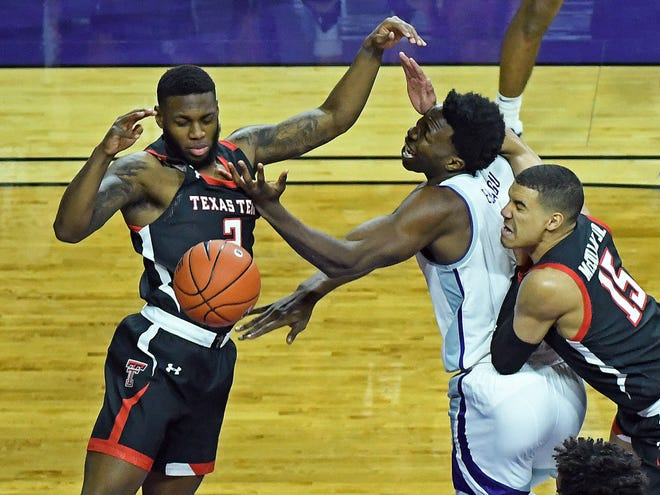 Kansas State center Kaosi Ezeagu, center, battles Texas Tech's Jamarius Burton (2) and Kevin McCullar for a loose ball during Saturday's game at Bramlage Coliseum.