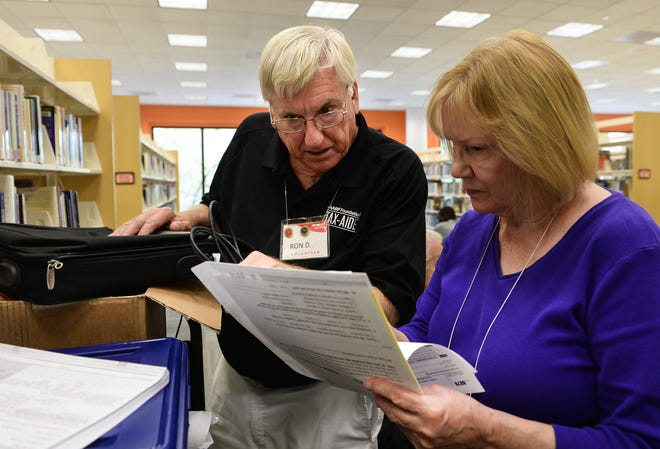 In this 2019 archive photo, AARP Tax-Aide site manager Ron DiLonardo, left, and volunteer Ransi Stephenson review a tax filing at the Selby Public Library. All tax filings are reviewed by another volunteer to ensure quality control.