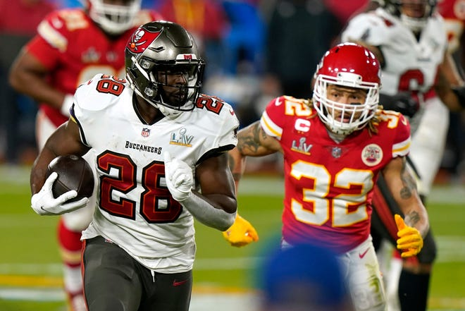 Tampa Bay Buccaneers running back Leonard Fournette (28) runs the ball as Kansas City Chiefs strong safety Tyrann Mathieu (32) pursues during the first half of the NFL Super Bowl 55 football game Sunday, Feb. 7, 2021, in Tampa, Fla. (AP Photo/Lynne Sladky)