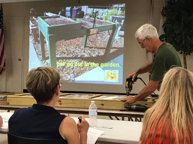 Master gardener volunteer John Dawson teaches a workshop on building a salad table.