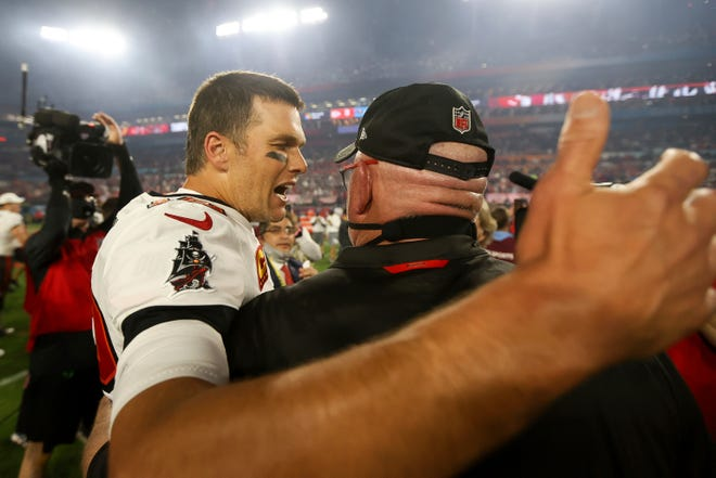 Tampa Bay quarterback Tom Brady celebrates with head coach Bruce Arians following NFL Super Bowl 55 Sunday. Brady said after the game that he will return to the Buccaneers next year.
