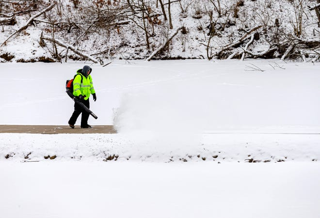 """Mark Woods, with the Springfield Park District, clears a fresh layer of snow from the path of the lower lagoon in Washington Park in Springfield, Ill., Monday, February 8, 2021. """"It's cold,"""" said Woods of working in temperatures hovering in the teens. """"If I keep on moving I'm alright."""" [Justin L. Fowler/The State Journal-Register]"""