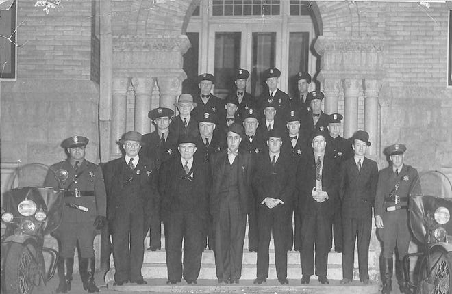 By the end of 1938, the Shawnee Police Department had proven themselves worthy of the task of keeping the citizens of the city protected from the criminal element. FRONT ROW (from left): Earnest Coleman, motorcycle officer; Chief of Police F.A. Budd; Sam Martin, assistant chief; Jack Cook, captain; Leo Timmons and King Faucette, plainclothesmen; Leonard Mayberry, radio technician; and C.D. Yates, motorcycle officer. SECOND ROW: Jason Varnell and C.L. Crittenden, desk sergeants; Bill Sullivan, Bill Holt, and Harve Tolson, patrolmen. THIRD ROW: A.I. Brown, merchant police; L.M. Lamb, C.D. Farrall, and Bill Jones, patrolmen. BACK ROW: C.W. Wheaton, C. Roberts, Walter Burger, and Paul Fruit, patrolmen. This photo was taken January 8, 1939.