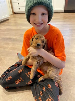 Miles Isbell, 9, hold his new puppy Charlie.