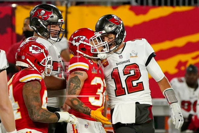 Tampa Bay Buccaneers quarterback Tom Brady (12) talks with Kansas City Chiefs strong safety Tyrann Mathieu (32) after throwing a touchdown pass during the first half of the NFL Super Bowl 55 football game Sunday, Feb. 7, 2021, in Tampa, Fla.