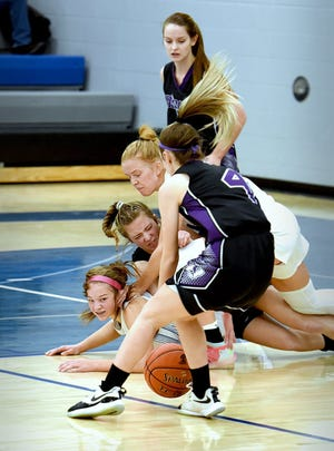 Collins-Maxwell's Reagan Franzen and Erica Houge get in a scrum with a Baxter player going after a loose ball during the No. 13 Spartans' 64-42 win over the No. 12 Bolts Saturday in Maxwell. The win avenged Collins-Maxwell's loss to Baxter earlier in the week.
