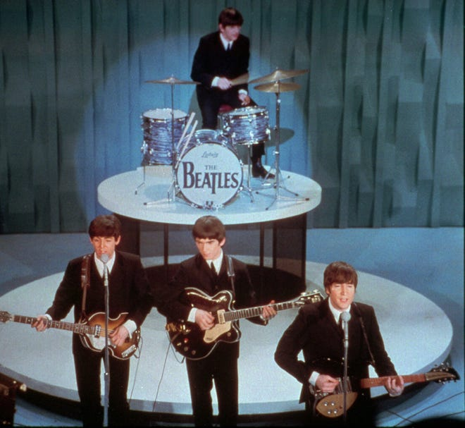 "The Beatles perform on the ""Ed Sullivan Show"" in New York on Feb. 9, 1964.  From left, front are, Paul McCartney, George Harrison and John Lennon. Ringo Starr on drums. (AP Photo)"