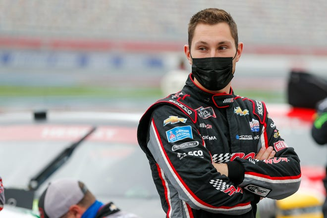 Kaz Grala stands by his car before a NASCAR Xfinity Series race last October.
