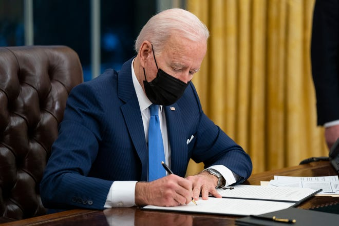 President Joe Biden signs an executive order on immigration Feb. 2 in the Oval Office of the White House in Washington.