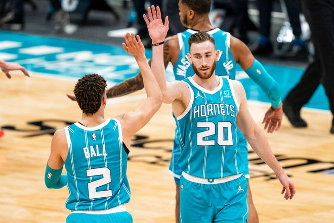 Charlotte Hornets forward Gordon Hayward (20) congratulates guard LaMelo Ball (2) who made a three-point basket against the Washington Wizards during the first half of an NBA basketball game in Charlotte, N.C., Sunday, Feb. 7, 2021. (AP Photo/Jacob Kupferman)